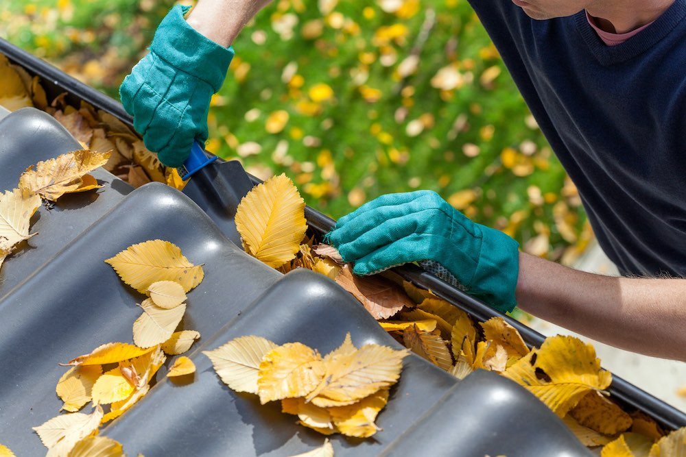 cleaning out clogged gutters from a roof